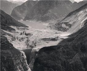 The lake behind the Vajont Dam, surrounded by forested mountains, and mostly filled with mud and debris.