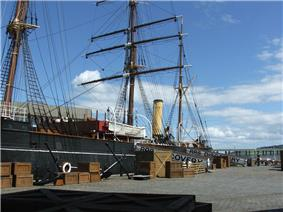 Partial view of a ship moored to a quayside. Prominent visible features are a mast with three crossbeams, two smaller masts, a funnel, a lifeboat and rigging. Packing cases are lined up on the quay, and a gangplank with