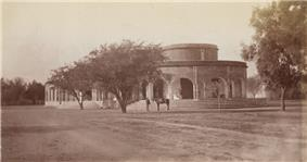 Old photo of low, round building with trees, a man and a horse in front