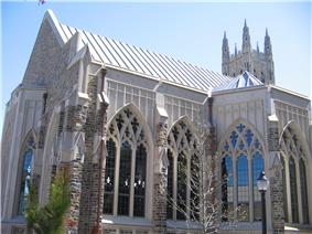Cathedral-sized arched and intricate windows on chapel are displayed prominently in foreground with larger soaring chapel peaking out at the top