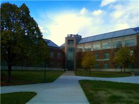 Picture of a three story building with walkways on an autumn day