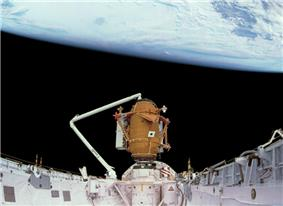 A space shuttle payload bay, covered in white insulation, with a small, cylindrical orange module at one end, supported by the shuttle's robotic arm. The blackness of space and the Earth serve as the backdrop.