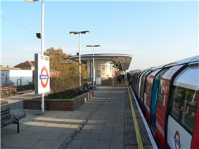 People walking on a railway platform with a train on the right with white siding and red doors all under a blue sky with white clouds