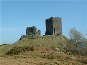 upon a grassy hillock stands two rectangular built fortifications. The one to the left is ruinous whilst the one to the right appears whole with battlements