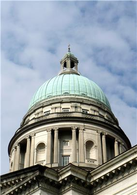 The dome of a building with a green patina, against a blue sky with clouds in it.