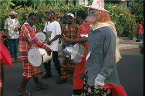 Band members performing on drums while in the street; one member is wearing a monkey mask and comic hat.
