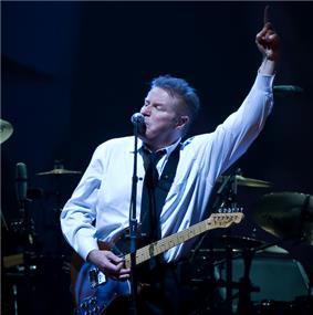 A man wearing a black tie and white dress shirt with an electric guitar hanging from a strap around his neck. His left arm is raised, with his index finger pointed upwards. In the background is a drum set.