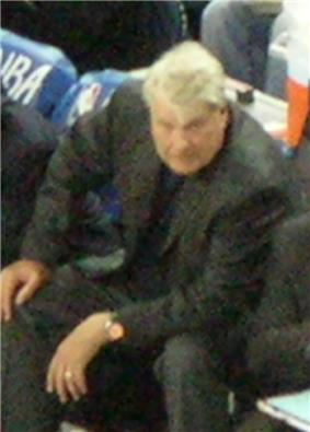 An older man, wearing a black suit, is sitting on the side of a basketball court.