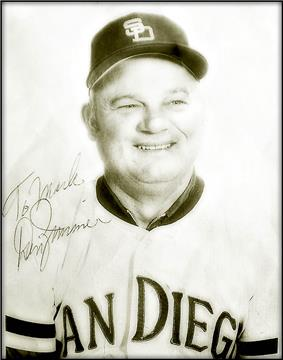 A middle-aged man wearing a light-colored San Diego baseball uniform; the photograph bears a signature saying
