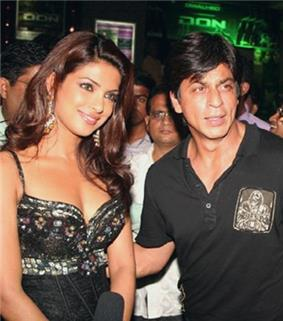 Shah Rukh Khan standing beside Priyanka Chopra at film premiere