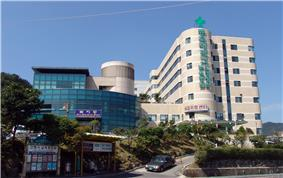 A large seven-story hospital complex on a slope that consists of about two buildings. The wall of one on the left is covered with blue glasses, and the other building with round corners is covered with beige bricks. Large green vertical signs are attached on the wall of the latter. The signs say