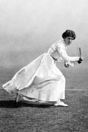 A black and white picture, a woman is in all-white attire hitting a right-handed one handed backhand with a racket in her right hand