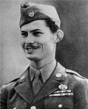 Head and shoulders of a young white man with a thin mustache wearing a garrison cap and a military jacket with two rows of ribbon bars and a round pin on the left breast.