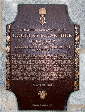 A bronze plaque with an image of the Medal of Honor, inscribed with MacArthur's Medal of Honor citation. It reads:
