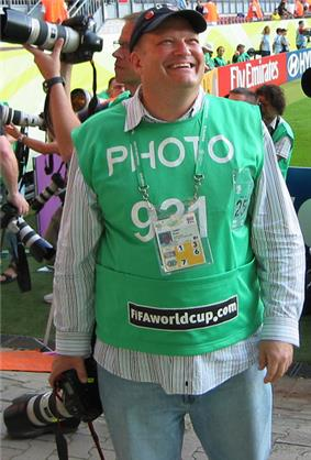 Carey smiling broadly, minus his usual glasses and in casual clothes with a green contest entry top. He is holding a camera with a long lens.