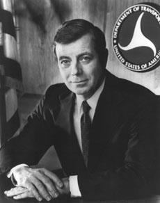 Black-and-white photo of a man wearing a suit sitting at a desk with his hands folded on it and the DOT logo and US flag behind him