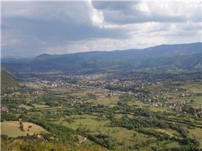 a panoramic photograph of a wide green valley with a small town in the middle distance