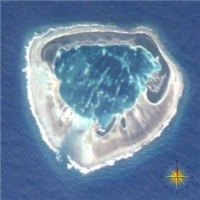 A satellite photograph of an atoll consisting of four islets with an interior lagoon. The largest island has a