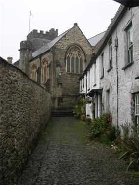 Stone building with arched windows and square tower seen at the end of a narrow lane with white painted houses on the right and a wall on the left.