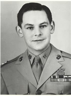 Head and shoulders of a young white man with neatly combed dark hair wearing a light-colored military jacket with three rows of ribbon bars and a parachute pin on the left breast.