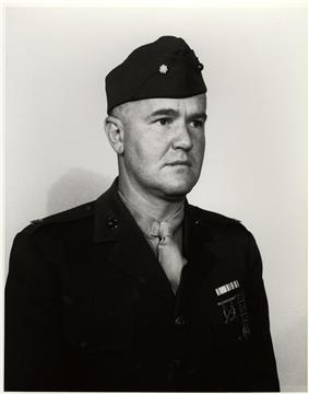 Head and shoulders of a white man wearing a garrison cap with an oak leaf on the side and a dark military jacket a row of ribbon bars and two badges on the left breast.