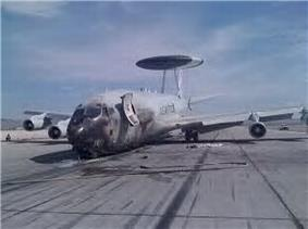 Jet aircraft resting on ramp with a nose-down attitude. The nose was blackened during a fire. On top of it is a circular radar.