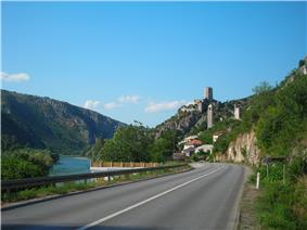 A view of a two lane road taken from a car. The road approaches a sharp left bend and a town, with a steep hill on the right and a river on its left.