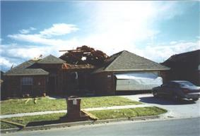 EF1 damage example -- Sections of roofing are removed from the home, leaving the internal decking exposed.