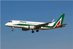 A white, green and red Embraer 175 aircraft in landing configuration.