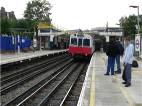 Red-and-white train pulling into outdoor station, with passengers waiting on platform