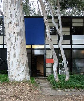 Photograph of the Eames House, a boxy building with a face of rectangles of various colors and clear glass, shaded by tall eucalyptus trees.