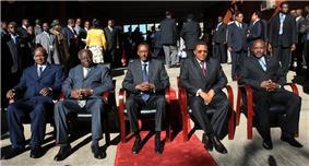 Five Presidents seated on chairs in an outdoor scene with sunshine and a red carpet: Yoweri Museveni of Uganda, Mwai Kibaki of Kenya, Paul Kagame of Rwanda, Jakaya Kikwete of Tanzania and Pierre Nkurunziza of Burundi