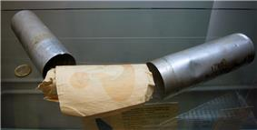 Two metal canisters resting on a glass shelf with a roll of papers, on which a question mark is visible, in between them. A two-euro coin is positioned to the left to provide a scale.