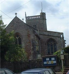 Red and grey stone building with arched windows and triangular roof. Behind is a small square tower