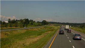 A four-lane divided highway among short hills travels into the background and curves to the right. The two divided halves are separated by a depressed swampy median.