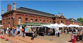 A wide, one story red brick building with a sloping black roof behind numerous white-topped tents selling assorted wares.