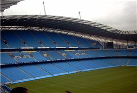 Roughly the same camera position shows grass up to the blue seats of the stands. The stand is now split into three tiers of permanent seating.