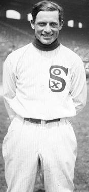 A man in a white baseball uniform smiles at the camera. He is shown from the knees up. His uniform shows the word