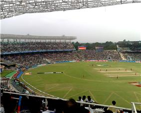 View from the top of a cricket ground during a cricket match, focusing on one side of the crowd; players are visible in the field.