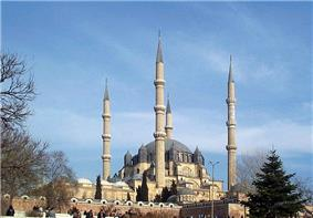 Large mosque with four minarets and a large dome of dark stone.