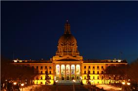 Provincial Legislature of Alberta lit up by exterior lighting during a winter night.