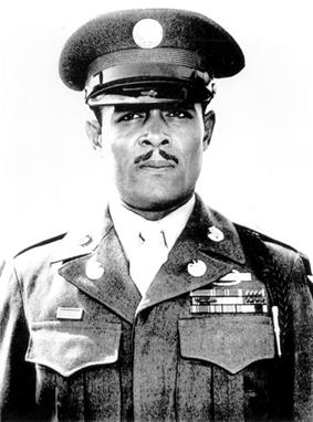 Head and shoulders of a black man, with a carefully trimmed mustache, standing erect and staring directly into the camera. He is wearing a peaked cap and a jacket with three rows of ribbon bars and a pin on the left breast, pins on the lapels, and a braided cord over the left shoulder.