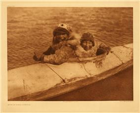 Photo of two males wearing fur sitting in well of large kayak