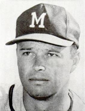 Bust portrait of a man in a white jersey with a dark stripe around the neck. He is wearing a dark baseball cap with a white