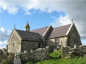 A stone church with slate roofs seen from the southeast. To the right is the chancel, to the left is a large transept, beyond which can be seen a bellcote