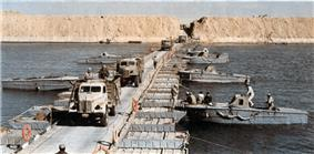 Military trucks crossing a canal on a pontoon bridge