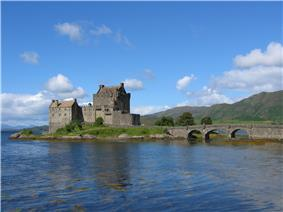 A stone castle in medieval Scottish style sits on a small island. An arched bridge leads off to the left.