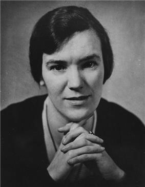 A black-and-white photograph of a middle-aged woman facing the camera. She had dark black hair and has her hands clasped. She is wearing a plain necklace and earrings.