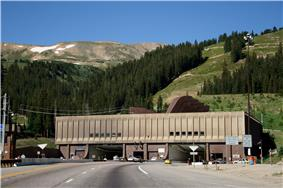 Automobiles are driving on a road leading to one of two openings in a building against a mountain. Letters above each opening read