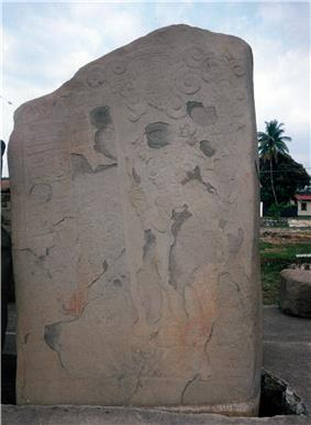 An upright stone slab with faint relief sculpture, badly flaked in places.